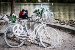 Peaceful Romance At The Shore. Two lovers sitting on the shore next to a bicycle decorated with white roses and a peace sign Royalty Free Stock Photo