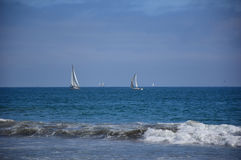 Peaceful sailing boat in open ocean at distance with blue sea stock photography
