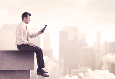 Peaceful sales guy sitting on roof top Stock Image