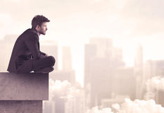 Peaceful sales guy sitting on roof top Royalty Free Stock Photo