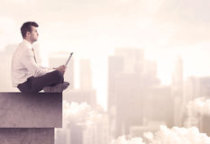 Peaceful sales guy sitting on roof top Royalty Free Stock Image