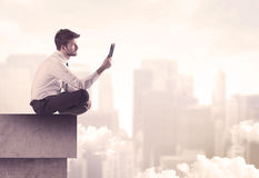 Peaceful sales guy sitting on roof top Stock Photography