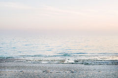 Peaceful scene of a calm sea at sunset. Pastel colors Stock Images