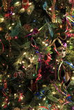 Peaceful scene of of Christmas tree with Mardi Gras theme. Pretty Mardi Gras theme Christmas tree covered with colorful baubles and string of lights Royalty Free Stock Photo