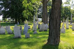 Peaceful scene with old weathered headstones in Revolutionary War Cemetery, Salem, New York, 2016. Peaceful scene with several worn headstones placed in memory stock image