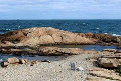 Peaceful scene of rocky shore with waves making their way to the beach. Pretty day with sunny skies and waves making their way to rocky shore, where beach chair royalty free stock photography
