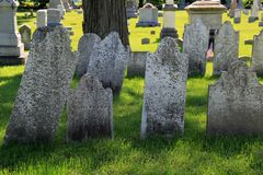 Peaceful scene with old weathered headstones and tombs set in Revolutionary War Cemetery, Salem, New York, 2016. Peaceful scene with several worn headstones and royalty free stock photography