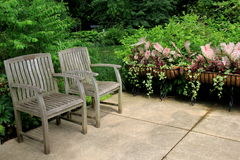 Peaceful scene of two wood chairs in corner of garden Stock Image