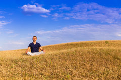 The peaceful scenery of a man meditating in the lotus position. Stock Photo