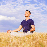 The peaceful scenery of a man meditating in the lotus position. Stock Photography