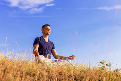 The peaceful scenery of a man meditating in the lotus position. Stock Image