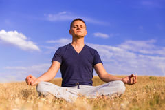 The peaceful scenery of a man meditating in the lotus position. Royalty Free Stock Photos