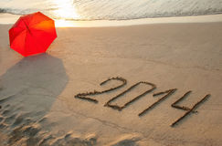 Peaceful seashore with 2014 drawn on  sand Stock Photos