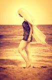 Peaceful sensual woman walking on beach sand. Artistic portrait of peaceful woman walking on the beach royalty free stock photos