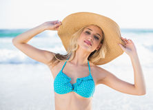 Peaceful sexy blonde in bikini wearing straw hat Stock Photography