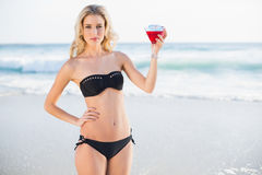Peaceful sexy blonde in elegant bikini holding cocktail Royalty Free Stock Image