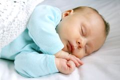 Peaceful Sleeping Newborn Infant. A sweet newborn infant girl is sleeping peacefully while snuggled in warm white blankets Royalty Free Stock Photography