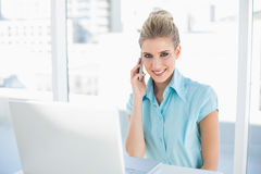 Peaceful smart businesswoman on the phone while using laptop Royalty Free Stock Photography