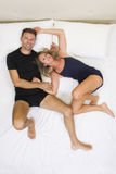 Peaceful and smiling couple holding hands in bed Stock Photos
