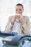 Peaceful sophisticated businesswoman smelling coffee. In bright office royalty free stock image