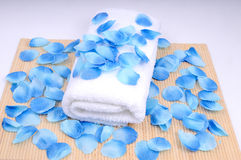 Peaceful spa set. Spa preaparation - white towel covered with blue petal royalty free stock images