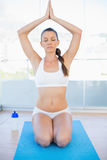 Peaceful sporty woman sitting in yoga position on exercise mat Royalty Free Stock Photos