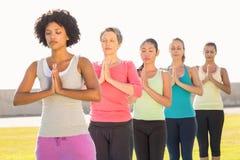 Peaceful sporty women doing prayer position in yoga class Stock Photos