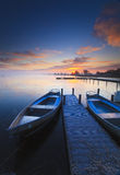 Peaceful sunrise with dramatic sky and boats and a Royalty Free Stock Photography
