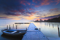 Peaceful sunrise with dramatic sky and boats and a. Jetty Royalty Free Stock Photo