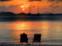 Peaceful Sunset. A man sits in one of two chairs on a beach and watches the sunset over a bay full of boats Stock Photography