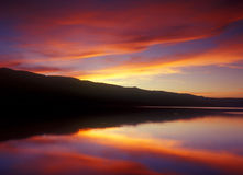 Peaceful Sunset on a Calm Lake. Brilliantly colorful sky at sunset reflecting in a perfectly calm lake stock photo