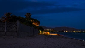 Peaceful and sunset almost night on the beach with some people m. Oving on the beach under artificial light in Sardinia Royalty Free Stock Image