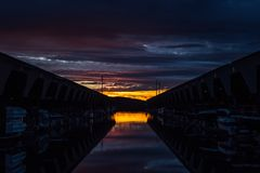 Peaceful Sunset over Sailboats at Dock. Sailboat sunset from Des Moines Marina in Washington State. The clouds give off a brilliant pink purple glow Royalty Free Stock Photo