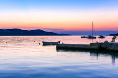 Peaceful sunset by the sea with boats and sailship Stock Photo