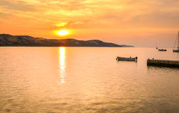 Peaceful sunset by the sea with boats and sailship Royalty Free Stock Photography