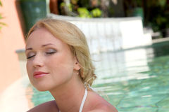 Peaceful time. Portrait of beautiful blond woman in swimming pool Stock Images
