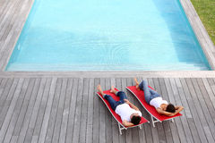 Peaceful time by the pool. Couple relaxing in long chairs by outdoor pool Stock Images