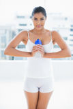 Peaceful toned brunette holding sports bottle Stock Photo