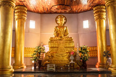 Peaceful. Tranquility in church with a golden Buddha and pole Royalty Free Stock Image