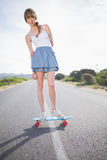 Peaceful trendy woman balancing on her skateboard Royalty Free Stock Photo