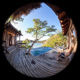 Peaceful tropical getaway. Two men relaxing in a peaceful pool overlooking the pacific ocean in Nicaragua shot with a fisheye lens creating a circl=ular effect Royalty Free Stock Photos