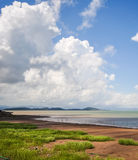 Peaceful view of cloudscape over shallow beach Stock Images