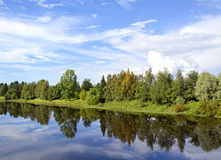 Peaceful view at the river in Finland. Beautiful summer evening by the river. Some boats are in the shore. Forest is reflecting from the water. Trees are royalty free stock photos