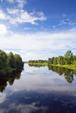 Peaceful view at the river in Finland. Beautiful summer evening by the river. Some boats are in the shore. Forest is reflecting from the water. Trees are stock image