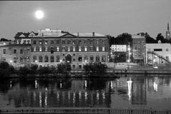 Black and white image of canal and historic buildings seen on the other side, Oswego, New York, 2016. Peaceful water running in front of old historic building Stock Photos