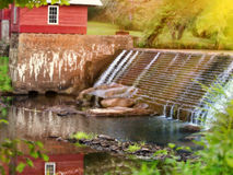 Peaceful Waters. On a sunny spring day water cascades and falls, past the old mill pond house into a pool of crystal clear water. Weeping willows on the river Royalty Free Stock Photography