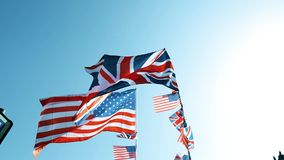 Peaceful waving British Union Jack and American flags of the United States. Waving slow motion against blue sky on a warm clear sky sunny marking the friendship