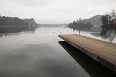 Peaceful winter on beautiful lake bled in slovenia. View on winter scenery landscape on empty wooden footbridge on scenic lake bled with view on island in cloudy Royalty Free Stock Photo