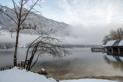 Peaceful winter nature. Beautiful lake Bohinj with wooden pier, mountains in background a mystical fog above it royalty free stock photo