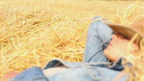 Peaceful woman with cowboy hat lying in hay stock video footage